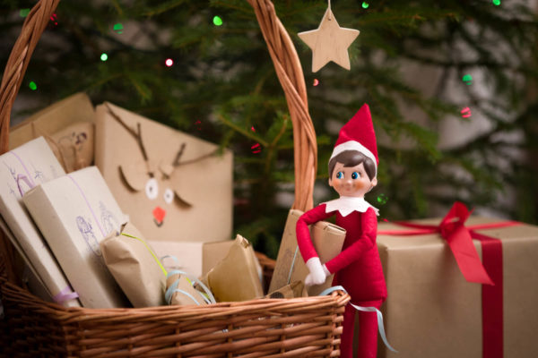 Elf on the shelf next to gifts