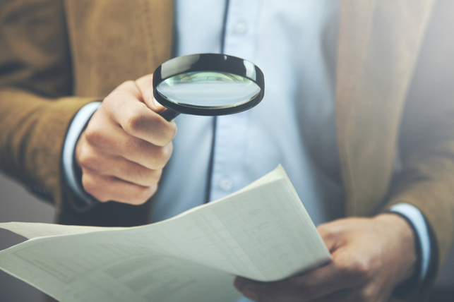 man reading document with magnifying glass