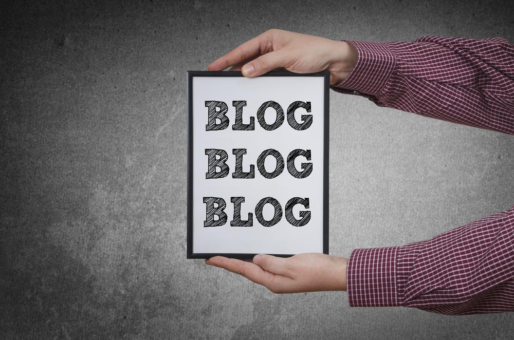"""hands holding sign that says """"blog blog blog"""""""