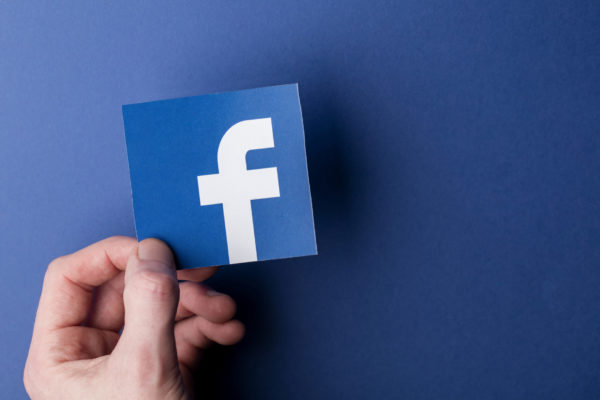 hand holding Facebook card icon