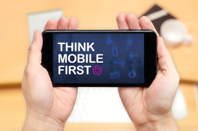 "hands holding phone that says ""think mobile first"""