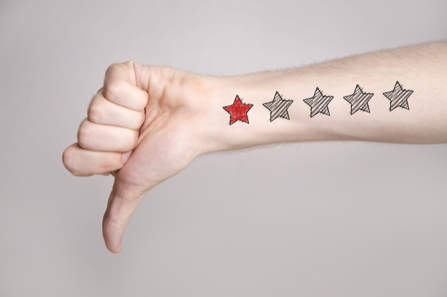 an arm pointing a thumb down, with one star scrawled in red on it