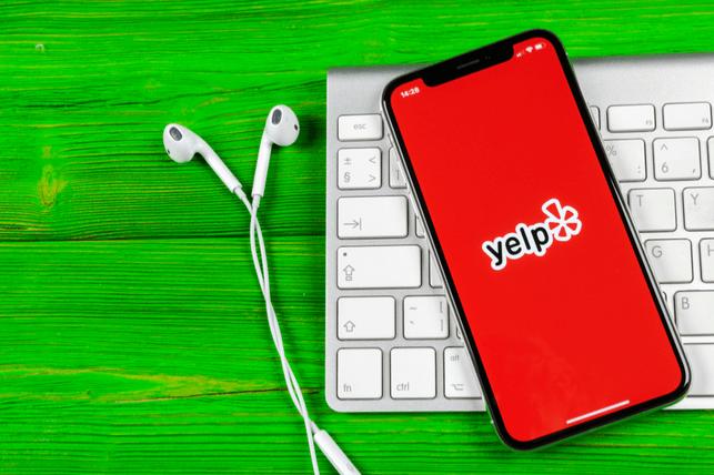 Phone with Yelp app open lying on keyboard