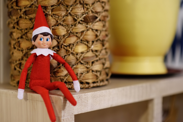 An elf sitting on a shelf.